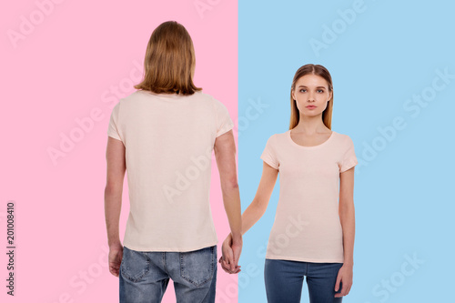 Different yet together. Well-built young man standing against a pink background with his back turned to the camera and intertwining his fingers with his girlfriend posing against blue background