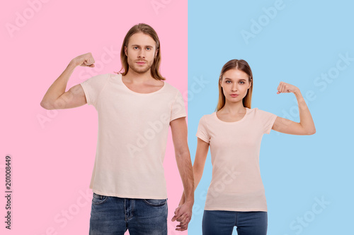 Razem silniejsi. Przyjemna młoda para trzymając się za ręce, przeplatając palce, jednocześnie podnosząc ramiona i pokazując ich biceps