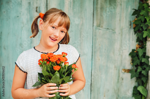 Outdoor portrait of a yong little girl of 9 years old, wearing white dress, holding fresh bouquet of beautiful orange roses