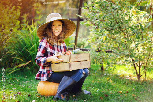 happy farmer child girl with autumn harvest - organic pumpkins, carrots and zuccini picked from own garden. Natural healthy life and food concept