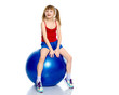 A little girl is jumping on the big gym ball.