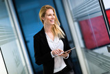 Portrait of successful businesswoman holding digital tablet - 201022608