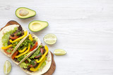 Tacos with pork, fresh vegetables, avocado, lime. White wooden background. Top view, flat, overhead. Copy space.