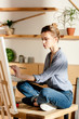 female artist sitting on table and drawing picture by paintbrush - 201023430