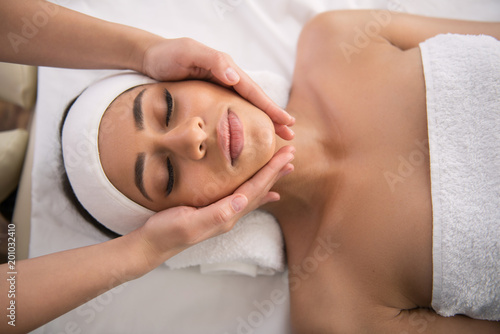 Peaceful expression. Top view of a beautiful woman closing her eye while feeling relaxed
