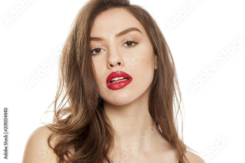 Foto Murales Young beautiful woman posing with red lipstick on her lips, on white background