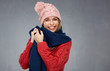 Quadro Smiling woman wearing knitted sweater, winter scarf and cup.