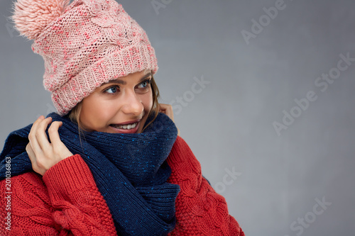 Foto Murales Smiling woman wearing warm winter clothes with kniteed hat and s