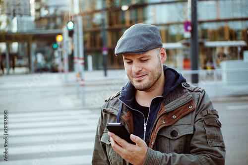 canvas print picture Mann beim lesen einer Nachricht am Smartphone in der Stadt