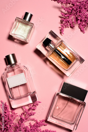Foto Murales top view of bottles of perfumes with pink flowers