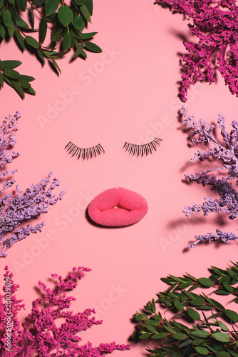 top view of face made of sponge and false eyelashes surrounded with flowers on pink surface