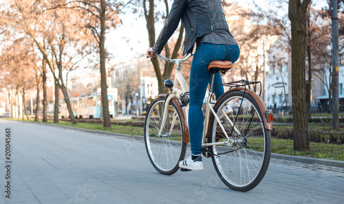 A girl in a leather jacket and jeans rides a bicycle along the avenue in the spring - 201045661