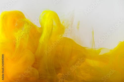 bliska widok mieszania farb żółty i brązowy rozprysków w wodzie samodzielnie na szary