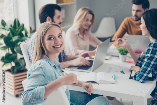 Beautiful, charming, stylish, pretty, cheerful, blonde woman in casual outfit sitting at the desktop with colleagues who discussing new project startup looking at camera enjoying working process