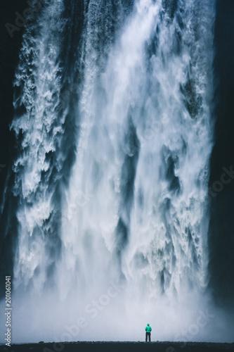 Hiker at gigantic Skogafoss waterfall in Iceland