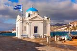 Agios Nikolaos Christian Church, typical Greek church building and Large waving Greek flag in Old Port of Mykonos City, Chora, on the island Mykonos, The island of the winds, Greece - 201067267
