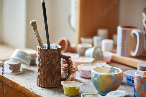 Foto Murales Close-up of various paint mugs and brushes in holder on worktop, selective focus, side view.