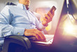 transport, tourism and technology concept - close up of businessman with smartphone and laptop traveling by plane and working over porthole background
