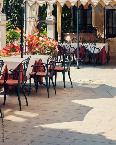 Outdoor restaurant empty tables and colorful flowers, Summer