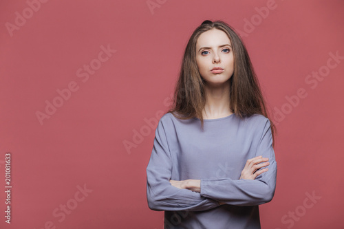Portrait of serious businesswoman being sure in herself, keeps arms folded, wears casual sweater, has staright dark hair, models against pink background with copy space for your advertizing content