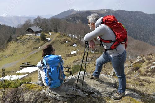 Foto Murales Hikers admiring mountain scenery during trekking day