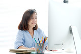 Young asian businesswoman working with laptop computer at office with happy emotion, working at home, office casual lifestyle concept - 201085297