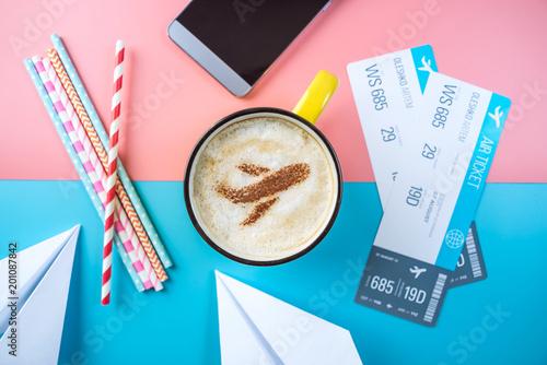 Kawowy cappuccino z obrazkiem samolot na pianie, odgórny widok. Pastelowe jasne tło. Pojęcie podróży lotniczych.