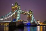 London, England - Iconic illuminated Tower Bridge by night with purple sky
