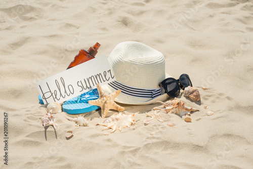 Foto Murales Hat on the beach, sunglasses, sea shells and a star and an inscription hi summer. On white sand