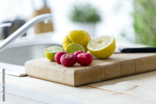 Lemon, lime and tomatoes on wood board in the kitchen at home.