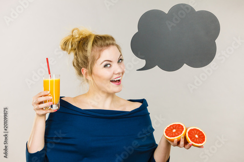 Happy woman holding fresh orange juice