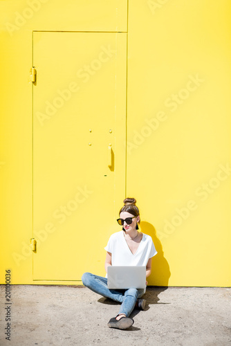 Woman working with laptop on the yellow wall background