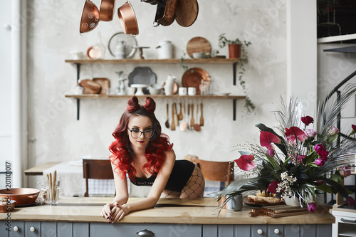 Beautiful and sexy pin-up model girl with red hair and professional makeup, in black bodysuits and glasses posing on a kitchen