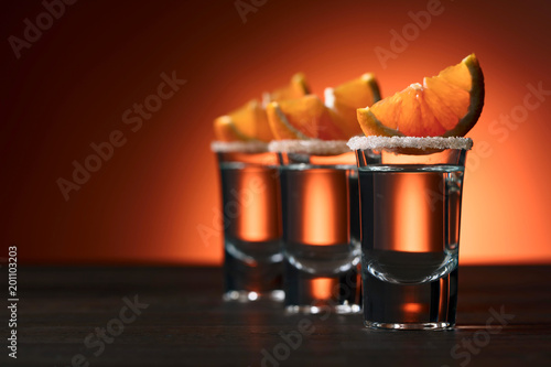 Glasses of alcoholic drink with orange slices, garnished with sugar and cinnamon powder.