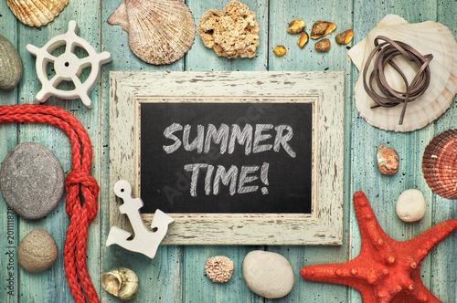 """Tablica z tekstem kredowym """"Letni czas"""", z muszlami morskimi, rybami sznurowymi i gwiazdowymi na jasnym drewnie"""