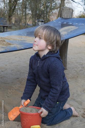 Niño (5 años) juega en un parque con un cubo y una pala.