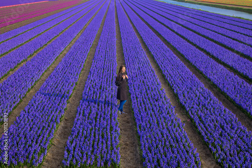 Foto op Aluminium Snoeien Beautiful young girl stands among flower fields. Top view.