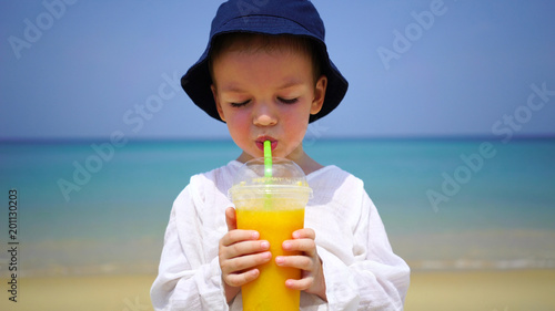 Fotobehang Sap boy of two years drinking mango fresh on the beach on the background of the ocean.