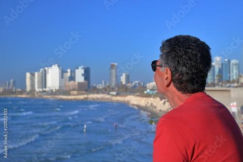 Satrszy mężczyzna z lekko siwiejącymi włosami, w czerwonej koszulce i okularach słonecznych, stoi bokiem i spogląda na panoramę zatoki Morza Śódziemnego, plażę i wyokie, nowoczesne budynki Tel Awiwu