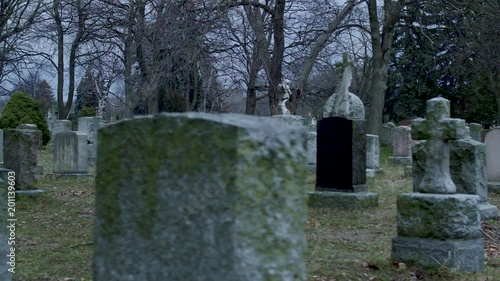 We are in a graveyard moving slowly across the moss covered tombstones. Evening.