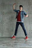Teenager guy in denim jacket and baseball cap, jeans and red sweater dances hip-hop. Dynamics of modern dance movement