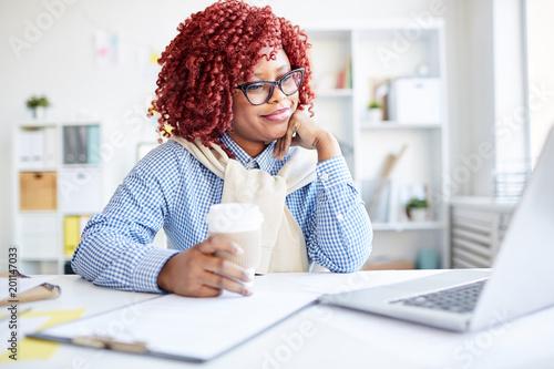Stylowy czarny pracownik biurowy kobieta z czerwonym kręconymi włosami siedzi przy biurku z kawa na wynos, czytanie wiadomości na laptopa i uśmiechnięty