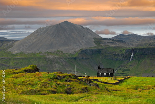 Iceland. Wooden church in the background of mountains and orange morning clouds - 201152600