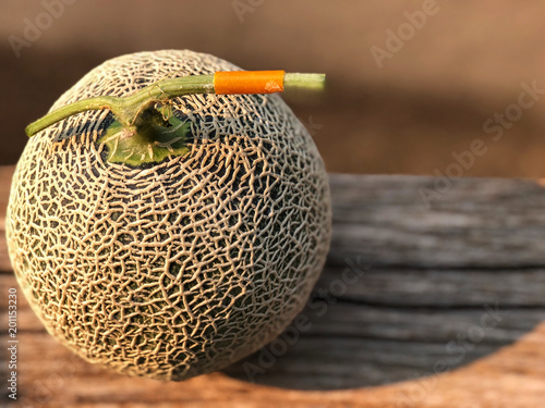Fresh Japanese melon on the wooden table and cement background with natural sunlight. Organic fresh farm. Top view and Copy space