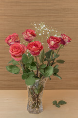 red roses with green leaves in a glass vase with water stand on a wooden table