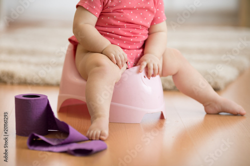 Closeup of legs of one year old baby toddler girl child sitting on potty in nursery room