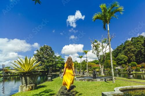 Foto Murales Woman in yellow dress traveler in the water palace of Tirta Gangga, Bali, Indonesia