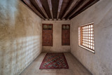 Room at El Sehemy house, a historic old Ottoman era house located in Cairo, built in 1648, with embedded wooden cupboard, wooden window and colorful carpet, Cairo, Egypt