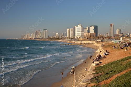 Widok na zatokę Morza Śródziemnego, plażę, nabrzeże ze spacerującymi i odpoczywającymi ludźmi, w tle wysokie nowoczesne budynki, Tel Awiw, Izrael, fale na morzu, błękitne niebo