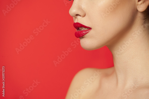 Foto Murales red glossy lipstick on red background